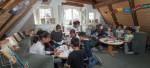 Kinder sitzen um zwei Tische und spielen Brettspiele