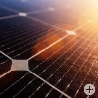 Detailaufnahme einer Solarzelle, auf die schräg von oben Lichtstrahlen einfallen